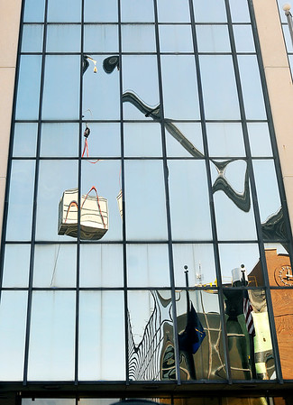 John P. Cleary |  The Herald Bulletin<br /> Workers lift a cooling tower for the new cooling system for the Madison County Government Center Thursday morning. This view is the reflection of the action off the windows First Merchants Bank across the street from the courthouse.
