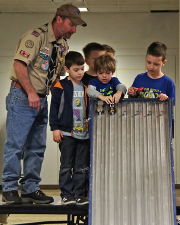 Under the watchful eye of event official Tim Chapman, Tiger Cub Scouts place their hand-built racecars in the starting gate at the Sakima District Pinewood Derby.