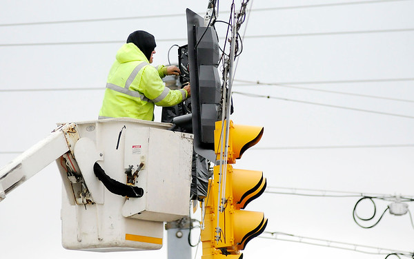 Don Knight | The Herald Bulletin<br /> A worker with Signal Construction Incorporated of Greenfield installs new traffic signals at the intersection of Mounds Road and Scatterfield on Wednesday. The new signals will included a flashing yellow arrow for permissive left turns and are part of a modernization of signals on state highways.