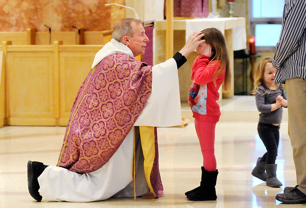 Don Knight | The Herald Bulletin<br /> Msgr. Robert Sell places ashes on the forehead of parishioners during Ash Wednesday Mass at St. Ambrose. Ash Wednesday is the first day of Lent.