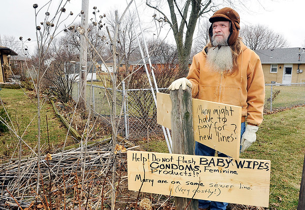 John P. Cleary |  The Herald Bulletin<br /> Mike Cloncs put up these signs on the edge of his property to help warn the neighbors of what type of products not to flush do to the ongoing sewer problems that Cloncs has experienced.