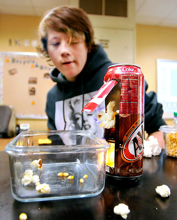 John P. Cleary |  The Herald Bulletin<br /> Recycle & Reuse projects from Cyndee McFarran's 8th-grade Alexandria-Monroe Jr. High School science class. Mark Goins demonstrates his Tin Popper for popping popcorn made with two pop cans and small candles.