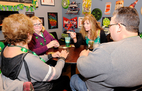 Don Knight | The Herald Bulletin Clockwise from left, Linda Grosswiler, Nicki Spence, Justine Hiles and David Spencer play a game of euchre during the St. Patrick's Day party at the Kettle Top Brewhouse on Saturday.