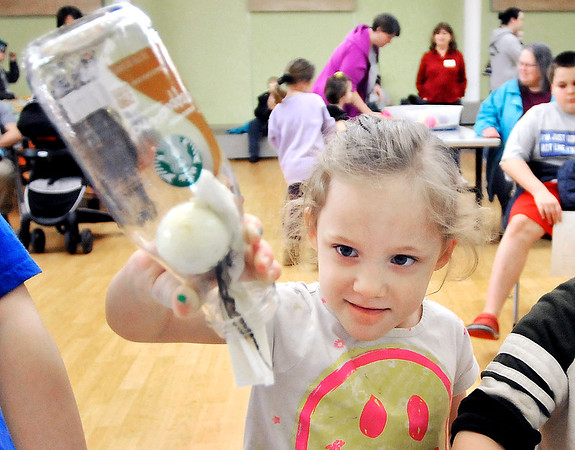 John P. Cleary | The Herald Bulletin<br /> Martha Guyer, 5,  takes a closer look at the egg inside this bottle as she turns the bottle over trying to get the egg out during the Eggs-periments for Kids event at the Anderson Public Library Monday.