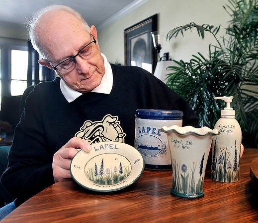 John P. Cleary   The Herald Bulletin<br /> Herschel Hinkle, a founding member of the Lapel Community Association, looks over some of the different pottery items they have had made to sell at the Village Fair each year to help raise funds for their different projects.