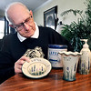 John P. Cleary | The Herald Bulletin<br /> Herschel Hinkle, a founding member of the Lapel Community Association, looks over some of the different pottery items they have had made to sell at the Village Fair each year to help raise funds for their different projects.