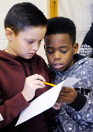 Don Knight | The Herald Bulletin<br /> From left, Brayden Stevenson and Tyshaun Raymore check a list of students enrolled in PNC's savings program before accepting a students deposit at 10th Street Elementary School on Friday.