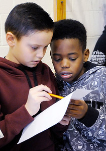 Don Knight | The Herald Bulletin From left, Brayden Stevenson and Tyshaun Raymore check a list of students enrolled in PNC's savings program before accepting a students deposit at 10th Street Elementary School on Friday.