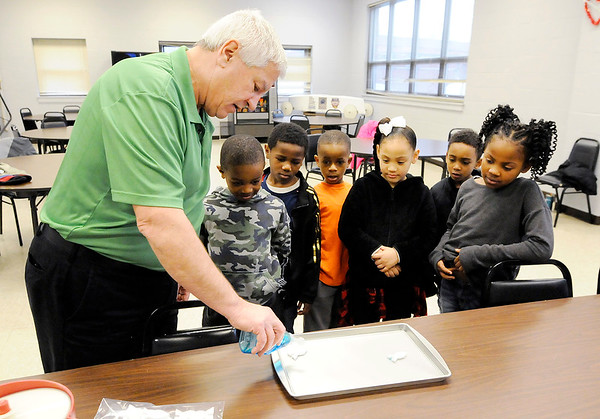 Don Knight | The Herald Bulletin<br /> Madison County Extension Director Gary Simmons demonstrates a surface tension experiment for students in the Spring Break Youth Camp at the  Anderson Township Trustee Youth Center on Tuesday.