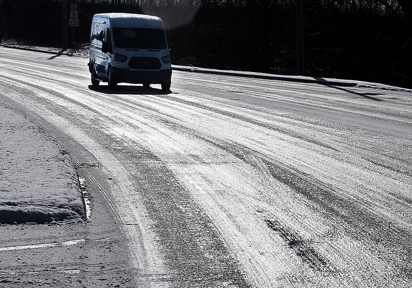John P. Cleary   The Herald Bulletin<br /> Early morning snow busts caused roadways to become a glaze of ice like this stretch of Mounds Road along the 2100 block.
