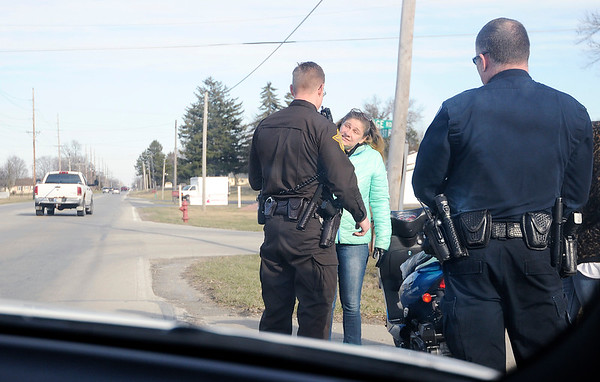 Don Knight | The Herald Bulletin<br /> John Vieke talks to a moped driver who was carrying a passenger on 53rd Street. You are not allowed to have passengers on a moped in Indiana.