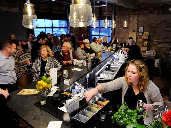Don Knight | The Herald Bulletin<br /> Layne Carpenter prepares a drink for a customer at Oakley Brothers Distillery during their grand opening on Tuesday.