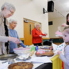 Don Knight | The Herald Bulletin<br /> Alana Fulton, 5, looks at a German display after sampling a Springerle cookie from Carole Hans and Virginia Clay at the Heritage club booth during the International Tasting Tour by the Madison County Extension Homemakers at the Madison County 4-H Fairgrounds Wednesday. The cookies were made by Hans and Suse Vinson. Over 100 people turned out for the event with booths from 18 Homemakers clubs.
