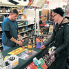 Manager Bruce Wright helps Jeffrey Taylor with his purchases Sunday at the Save-On Liquor store at Broadway and Vinyard streets in Anderson.