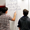 John P. Cleary | The Herald Bulletin<br /> One of the items that utilized in the classroom makeover is dry-erase storage closet doors to give more space for students to work out their math problems like these two AHS calculus students.