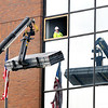 John P. Cleary | The Herald Bulletin<br /> This worker watches from a fourth-floor opening in the Madison County Government Center Tuesday as building material for the courthouse remodeling is raised up to him. The asbestos remediation is complete on the fourth and third floors with remodeling work starting on the top floor.