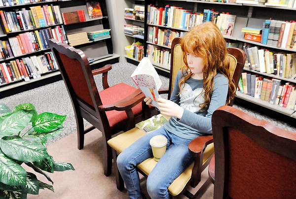 "Don Knight | The Herald Bulletin<br /> Carrie Chandler, 9, reads ""Umbrella Summer"" while waiting for her mom at The Book Nook on Saturday. The store is looking for a new location to move to."