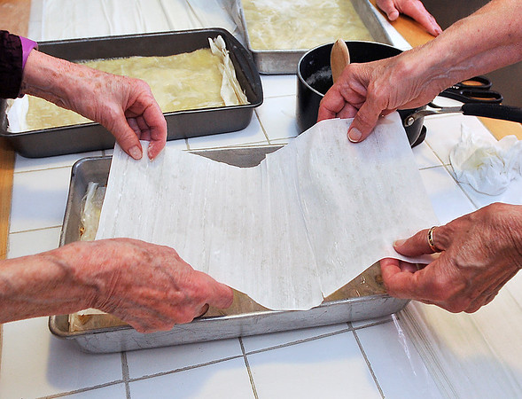 John P. Cleary   The Herald Bulletin<br /> Members of the Onward & Upward Homemaker's Club put another layer of phyllo dough over the filling as they build up the layers of the baklava.