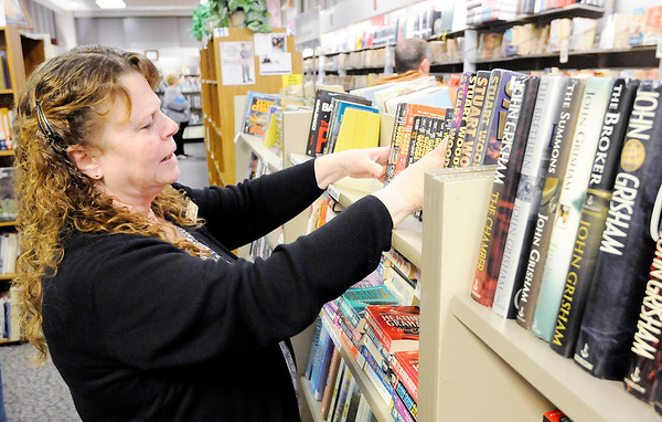Don Knight | The Herald Bulletin<br /> Madison County Coalition Director Ginger Mills straitens books on the shelves at The Book Nook. The store raises funds for the Madison County Literacy Coalition and depends on book donations to stock their shelves.
