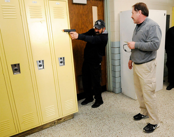 Don Knight | The Herald Bulletin<br /> Steven Guthrie, who retired from APD and now works for the Indiana Law Enforcement Acadamy, uses a locker for cover and support during training by Jim Huffman on a lone officer engaging an active shooter in a hallway during training at Northside Middle School.