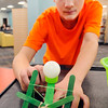 John P. Cleary | The Herald Bulletin<br /> Bryant Cox, 13, a sixth-grader at Highland Middle School, takes aim as he tries to hit the basket with his home-made catapult during the Kick Off March Madness - STEAM Style program at the Children's Department of the Anderson Public Library Monday.