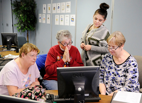 Don Knight | The Herald Bulletin<br /> Second from left, Peggy Hall waits in anticipation after submitting a tax return for Becky Hooper, left, as Monique Flores and Patti Sveum look on at the Impact Center on Thursday.