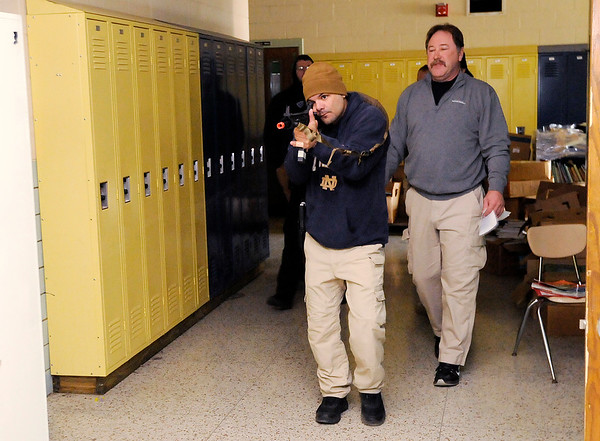 Don Knight | The Herald Bulletin<br /> Juan Galan with the Madison County Sheriff's Department moves down a hallway with his rifle shouldered as Jim Huffman leads a session on a lone officer engaging an active shooter in a hallway during training at Northside Middle School on Friday.