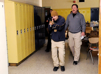 Don Knight | The Herald Bulletin Juan Galan with the Madison County Sheriff's Department moves down a hallway with his rifle shouldered as Jim Huffman leads a session on a lone officer engaging an active shooter in a hallway during training at Northside Middle School on Friday.