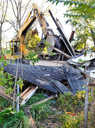 John P. Cleary |  The Herald Bulletin<br /> Workers from Fredericks Inc. demolish this vacant house in the 2200 block of Locust Street Tuesday morning. There were three houses earmarked for demolition in this block as part of the city's Blight Elimination Program.
