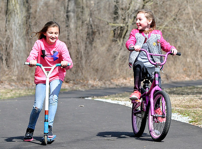 John P. Cleary | The Herald Bulletin Best friends Taylee Trahan, 9, and Sydney Webb, 9, enjoy the bright sun and above normal temperatures Monday, on their first day of spring break, riding around the trails of Shadyside Park. Both girls are third-graders at Tenth Street Elementary School. With spring starting officially at 11:15 a.m. Tuesday morning, the forecast calls for colder temperatures with a change of rain changing to snow.