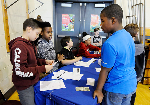 Don Knight | The Herald Bulletin<br /> From left, Brayden Stevenson and Tyshaun Raymore help Zy'treon Taylor make a deposit into his PNC savings account at 10th Street Elementary School on Friday.