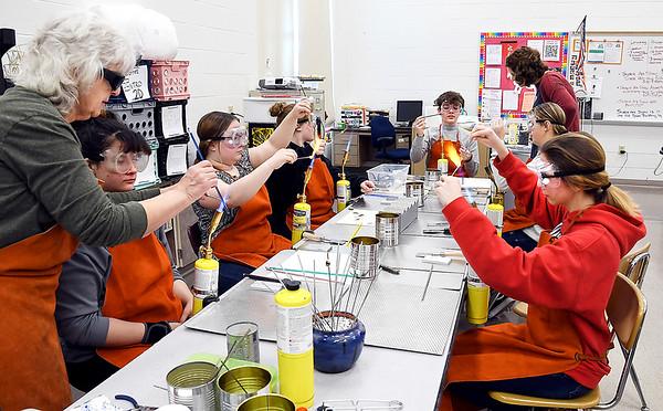 John P. Cleary | The Herald Bulletin<br /> Chic Elbert, far left, former AHS art teacher, shows students in Katherine Kester's AHS art class the technique in making glass beads.