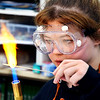 John P. Cleary | The Herald Bulletin<br /> AHS junior Kayla Lewis watches as she heats up her glass rod as she works to make glass beads in Katherine Kester's art class.