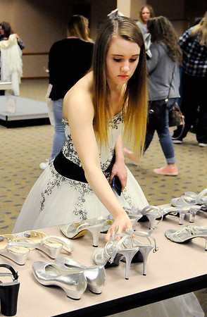 Don Knight   The Herald Bulletin<br /> After choosing a dress Ivory Wasson looks for a pair of shoes during Anderson Public Library's Project Fairy Godmother prom dress giveaway  on Saturday.