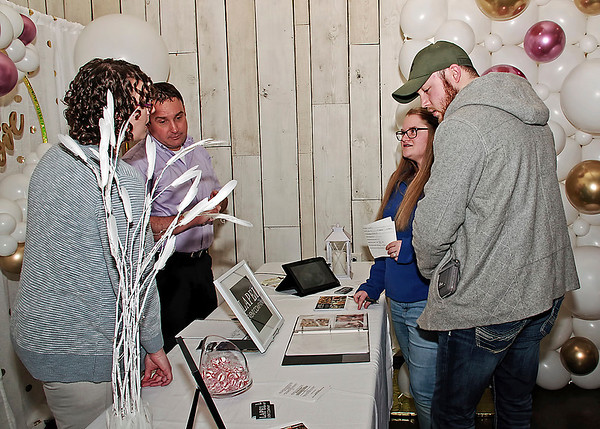 At the Crystal Coop Bridal Expo, Ethan Gallagher and Miracle Enyeart review the services available from Lapel Event Company with owners Michaele and David Sturgeon. (Mark Maynard photo)