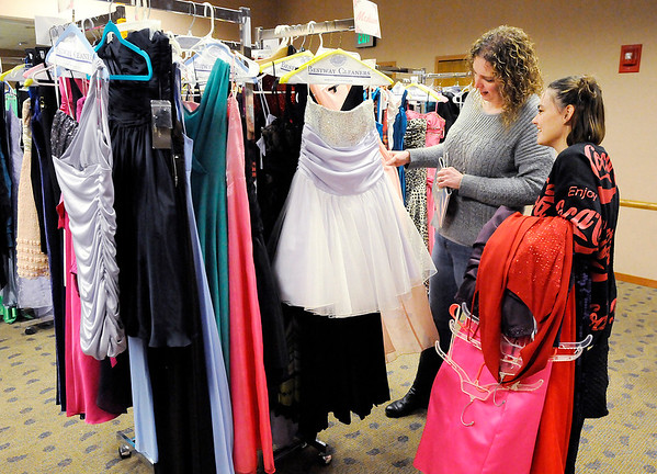 Don Knight   The Herald Bulletin<br /> Autumn Dalton helps Kylee Garrison pick out dresses to try on during Anderson Public Library's Project Fairy Godmother prom dress giveaway  on Saturday.