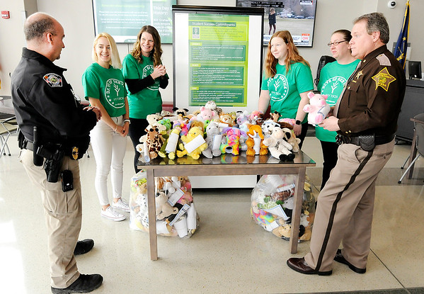 Don Knight | The Herald Bulletin<br /> Students at Ivy Tech's Anderson campus made stuffed animals for donation to the Madison County Sheriff's Department and the Community Hospital Anderson Police Department to be given to children in traumatic situations. From left are Community Hospital Police Chief Phil Caldwell, Viktoriia Popovych, Ashley Barclay, Melissa Wiley, Marra Widener, Brandi Foley and Joey Cole from the Madison County Sheriff's Department.