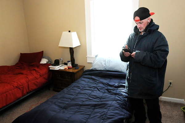Don Knight | The Herald Bulletin<br /> Cory Robinette listens to music on his phone at Grace House's new men's home. The home recently opened and it is already filled.