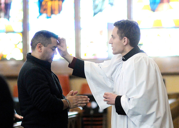 Don Knight | The Herald Bulletin<br /> Elliot Zak marks a cross on the forehead of Antonio Barajas during an Ash Wednesday service at St. Mary. Ash Wednesday is the first day of Lent.