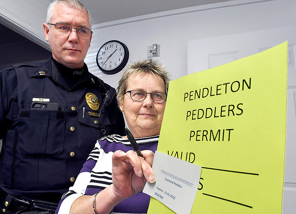 John P. Cleary | The Herald Bulletin<br /> Capt. Randy Sidwell, of the Pendleton Police Department, and Connie Whetsel, Pendleton records department, show the bright colored sign someone that is issued a peddlers permit from the town has to display at all times while conducting business in Pendleton.
