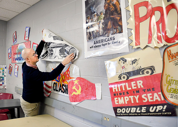 John P. Cleary | The Herald Bulletin Chris DeHart, a social studies teacher at Pendleton Juvenile Correctional Facility, decorates his classroom walls with materials used in his teaching.