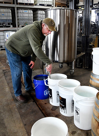 Jason Oakley checks these containers full of sanitizer that is for Community Hospital Anderson. The Oakley Brothers Distillery have converted from distilling whiskey to making the sanitizing solution. They are giving it to the public for free.