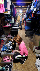 As Maci Dowden, 10, sorts shoes her mother, Jennifer Hicks, sorts through some of the donations hanging up in The Clothes Garden located in their Frankton home.