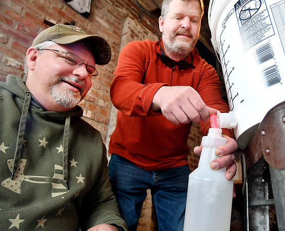 Jason and Jerrad Oakley, of Oakley Brothers Distillery, pour a bottle of hand sanitizer from a batch they have made. Since the onset of the COVID-19 crisis the brothers have converted from distilling whiskey to making the sanitizing solution. They are giving it to the public for free.