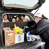 April Reed, food service director for Daleville Community Schools, loads the back of this SUV with bagged meals as the kids in the back of Christina Suronto's SUV look on. The Daleville schools provided 6,100 meals for families residing in the school system Wednesday morning with a drive-thru pick-up at the elementary school building.