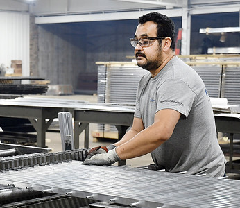 Barnett Bates employee Gabriel Mandoza inserts metal rods through the holes of the flat pieces to form a grate section at their manufacturing facility in North Anderson.
