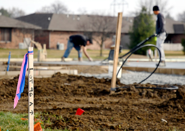 Lots are staked out as crews work on the foundation of a new home in South Main Village in Anderson.