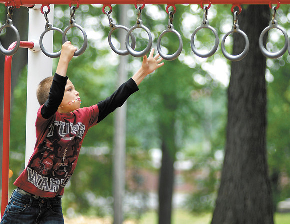 JosŽ Esparza, 8, reaches out for another ring as he plays at Warren Miller Park Monday afternoon on his first day of summer break from school.  Esparza goes to Anderson Preparatory Academy and they finished up their school year last Friday.