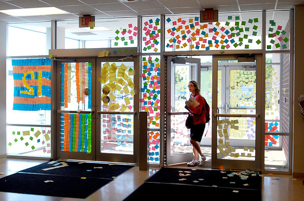 This Anderson High School student enters the south entrance of the building Friday morning that had been totally covered with Post-It notes as part of a senior class prank overnight.