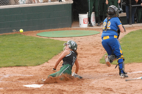 Kinzie Davis scores for the Arabians as the ball gets away from Greenfield catcher Brittany Hardwick.